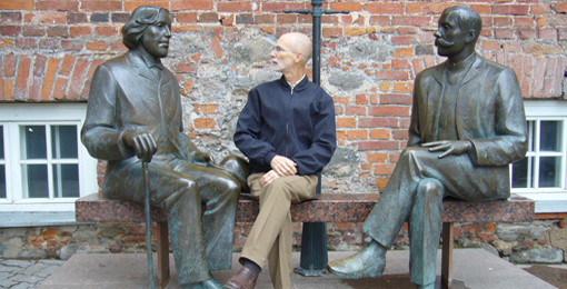 kuva Sisko Salo-Chydenius. Mies istuu kahden kirjailijan patsaan välissä.