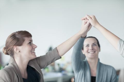 Kolme naista ovat nostaneet yhteen liitetyt kädet ylös ja hymyilevät.