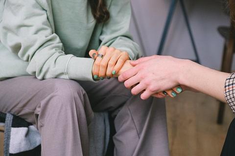 Henkilö pitää kädestä toista henkilöä.