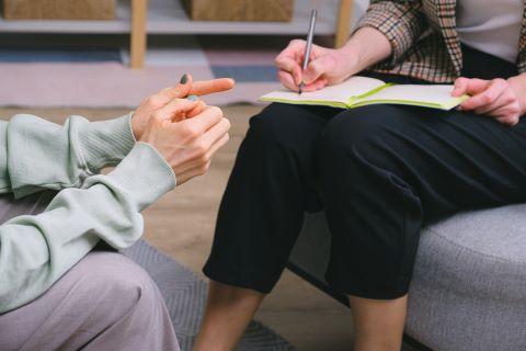 Kaksi naista istuu sohvalla, toinen kirjaa ylös keskustelua.