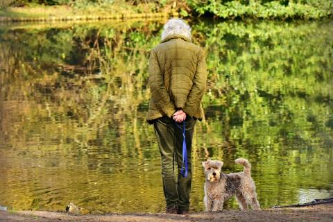 Ikääntynyt nainen seisoo koiran kanssa veden äärellä syksyissä luonnossa.