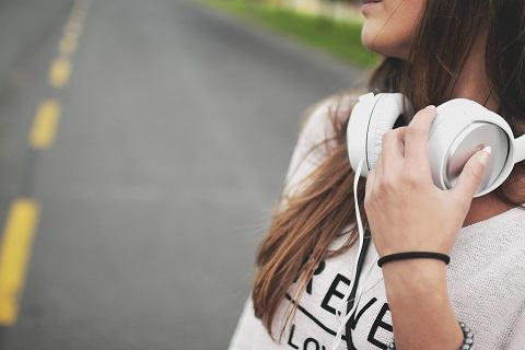 Tyttö ylittää tietä kuulokkeet kaulalla.