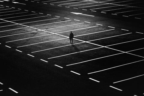 Öinen parkkipaikka kaukaa kuvattuna ja yksi tumma hahmo on sen keskellä.