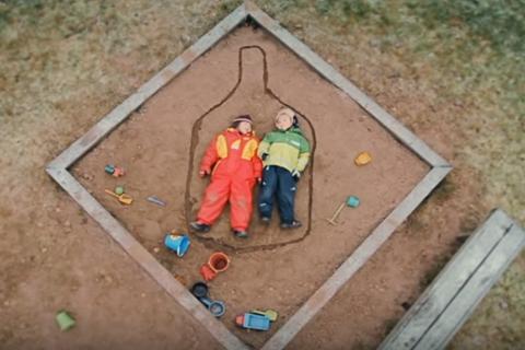 Kaksi lasta makaa vierekkäin hiekkalaatikolla ja heidän ympärilleen on piirretty hiekkaan pullon ääriviivat.