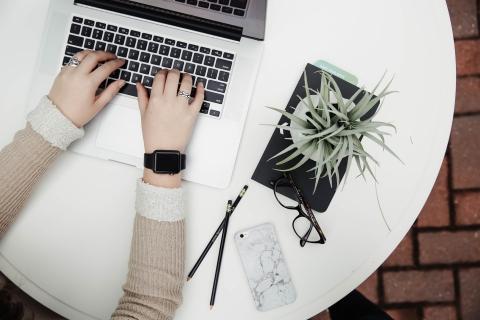 Naisen kädet tietokoneen näppäimistöllä.