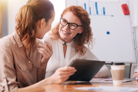 Kaksi naista juttelee tabletin ääressä.