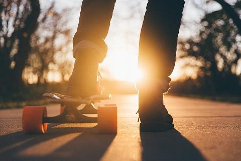 Skeittaava nuori ilta-auringossa.