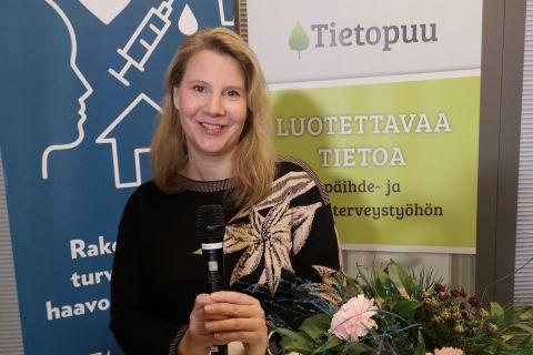 Tanja Vahter seisoo mikrofoni kädessä Tietopuu- ja A-klinikkasäätiö rolluppien edessä.