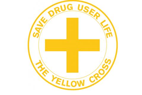 """Keltainen risti, jonka ympärillä on teksti """"Save Drug User Life, The Yellow Cross""""."""