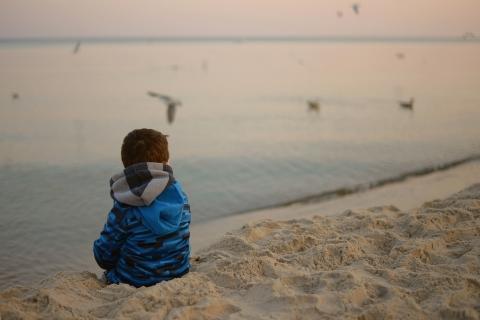 Pieni lapsi istuu rannalla ja katsoo merta.
