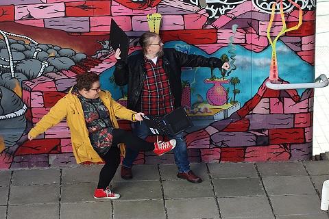 Kaksi henkilöä kävelee graffittikuvan edustalla ja toisella on tietokone kädessä.