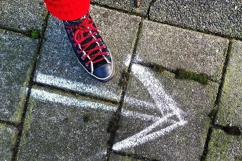 Maassa on liidulla piirretty nuoli eteenpäin ja kenkä osoittaa sitä.