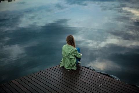 Nainen istuu selin laiturilla ja vedestä heijastuu pilvet.
