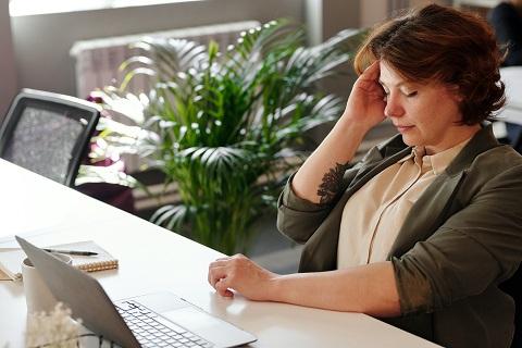 Nainen istuu tietokoneen äärellä ja pitelee toisella kädellä päätään silmät suljettuina.