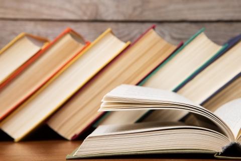 Kirjahyllyssä kirjoja ja yksi kirja avattuna.